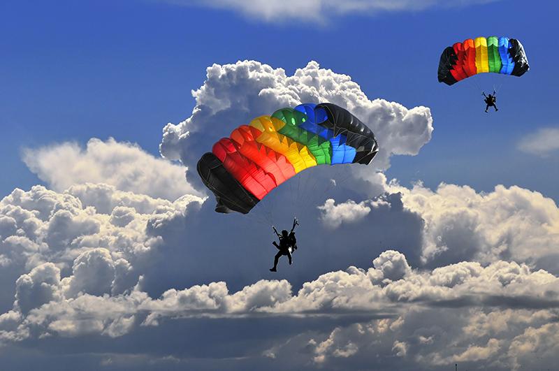 To fargerike fallskjermer mot blå himmel og skyer